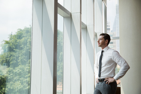Young businessman standing with hands on hips and looking through office window with blurry city view outside