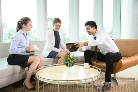 informal: Group of three business people holding informal meeting in modern office. Young businessman showing something on tablet computer to his female coworkers