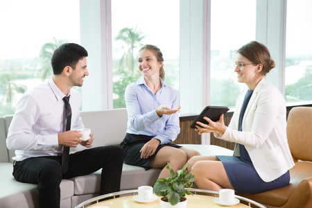 informal clothing: Group of three young business people sitting in modern office and having informal meeting. Businesswoman showing something on tablet computer to her colleagues, they smiling