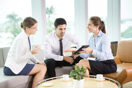 informal: Business team having informal meeting in modern office, discussing business project. Businesswoman showing presentation on tablet computer to her colleagues. Teamwork concept Stock Photo