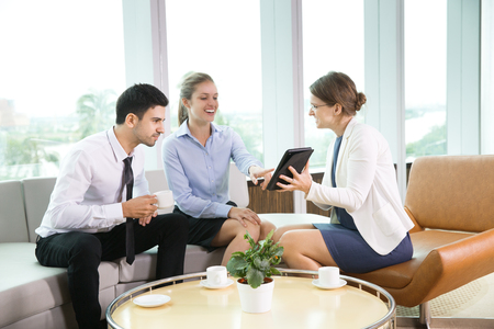 Equipo de negocios que tienen reunión informal en la oficina moderna, discutiendo proyecto empresarial. Empresaria que muestra la presentación en el ordenador de tableta a sus colegas