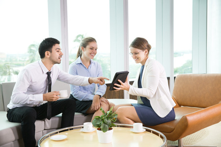 informal: Business team having informal meeting in modern office, discussing business project. Businesswoman showing presentation on tablet computer to her colleagues
