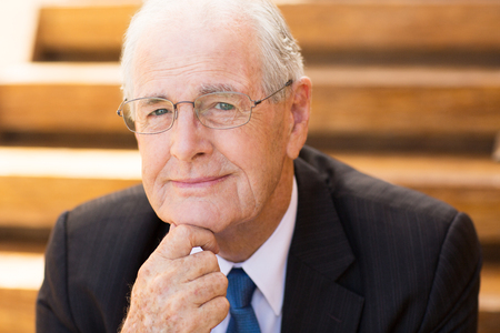 Portrait of mature grey-haired businessman sitting outside office, holding his chin with hand and smiling at camera