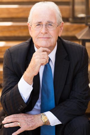Portrait of mature grey-haired businessman sitting outside office, holding his hand on chin and thinking over something