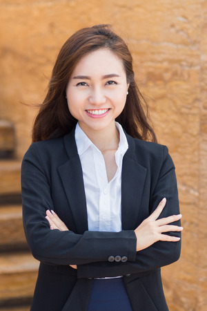 informal clothing: Portrait of young Asian businesswoman standing with crossed arms outside office and smiling at camera