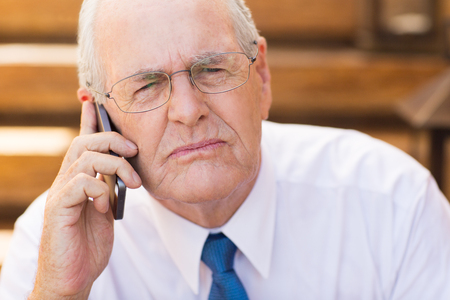 Portrait of senior businessman talking on smartphone about serious issues
