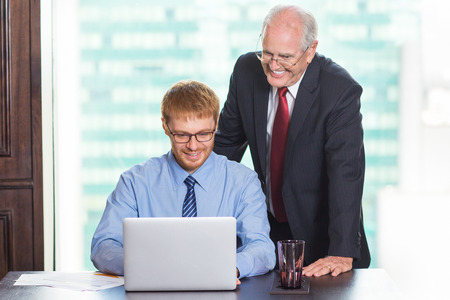 Senior businessman standing behind young colleague sitting at table with big window and blurry city view in background. They are smiling and looking at laptop screen. Stock Photo