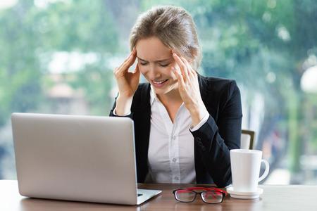 Jonge zakenvrouw zittend aan tafel in de voorkant van de laptop bij het sluiten van de ogen strak en aanraken tempels. Vooraanzicht met groot raam en wazig groen uitzicht naar buiten in de achtergrond. Stockfoto