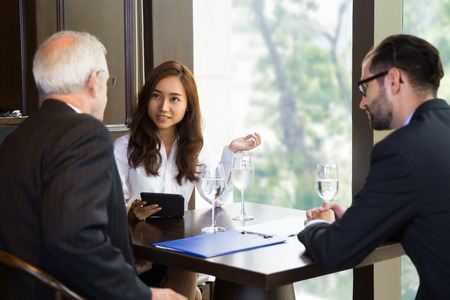 negotiating: Smiling young businesswoman, senior and young businessmen negotiating while sitting at small table in cafe near big window with blurry city view outside. Men are sitting back to camera. Stock Photo