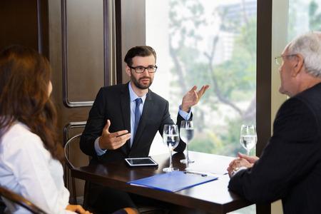 Hombres de negocios mayores y jóvenes y joven empresaria de negociación mientras está sentado en una pequeña mesa en la cafetería cerca de la ventana grande con vista borrosa ciudad fuera. Mujer y hombre mayor se sienta de nuevo a la cámara.
