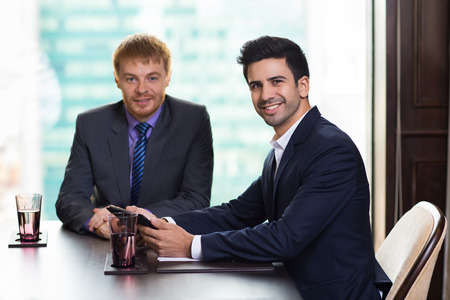 farther: Two young handsome businessmen smiling and looking at camera while sitting at table in meeting room with big window and blurry city view in background. Farther man is slightly blurred. Stock Photo