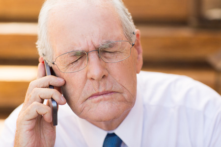 eyes closing: Close up portrait of focused senior businessman talking on mobile phone and closing his eyes
