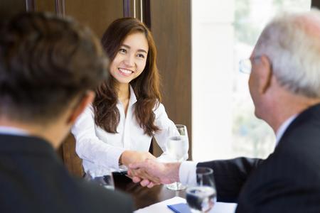 Portret van jonge Aziatische onderneemsterzitting in modern bureau en het schudden van handen met haar mannelijke partners na het eindigen van vergadering