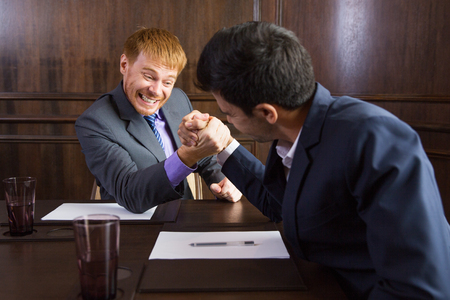 Two young businessmen sitting in modern office and arm wrestling. Business competition concept Stock Photo