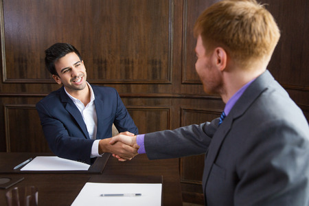 concluding: Young business partners sitting in modern office and shaking hands after signing contract. Partnership concept