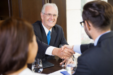 concluding: Portrait of senior businessman sitting in modern office and shaking hands with his partner after finishing meeting. Female assistant sitting nearby Stock Photo