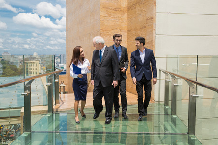 Group of four successful business people walking on open glass bridge between office buildings and talking. Communication concept