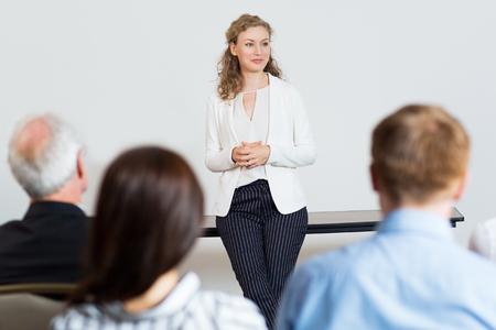 Portret van jonge vrouwelijke onderneemster die zich in conferentieruimte bevindt en aan vraag luistert. Bedrijfspresentatie concept Stockfoto