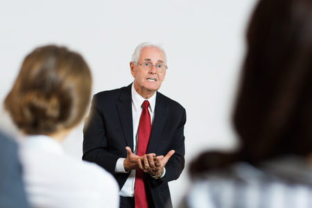 Closeup portrait of mature business expert standing with open hands gesture in front of audience at conference and explaining his business ideas