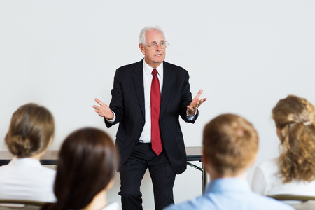 rhetorical: Portrait of successful senior businessman speaking in front of audience at conference, explaining ideas to his young colleagues