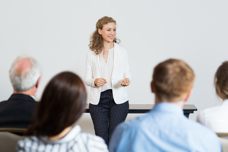 Portrait of successful young businesswoman speaking in front of audience at conference, making presentation to colleagues