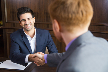 concluding: Portrait of young Caucasian businessman sitting in modern office and shaking hands with his partner after finishing meeting