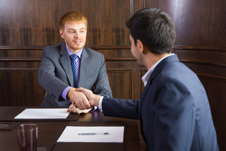 concluding: Portrait of young Caucasian businessman sitting in modern office and shaking hands with his male partner after signing contract. Partnership concept