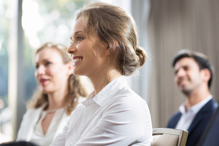 Smiling young businesswoman sitting and watching presentation with her male and female colleagues blurred in background