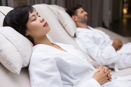 Young woman and blurred man in background wearing bathrobes and dozing on deckchairs in spa salon Stock Photo
