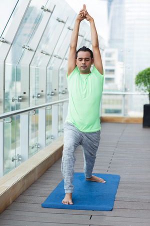 closed club: Young Indian man wearing sport clothes and practicing yoga on open terrace of modern fitness club, standing warrior pose with closed eyes. Yoga concept