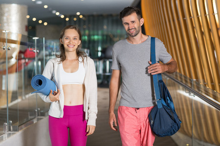 Portrait of smiling young woman and man with spots bag and mat wearing sportswear while standing and looking at camera in corridor of fitness center