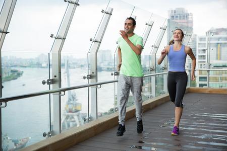 hombres corriendo: Sonriendo ropa deportiva joven hombre y mujer con y trotar en el balcón con valla de vidrio y vista del río y la ciudad exterior. Foto de archivo
