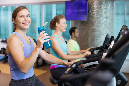 Smiling at camera young woman drinking water and another woman and man in background. Everyone is wearing sportswear and exercising on exercise machines in gym.