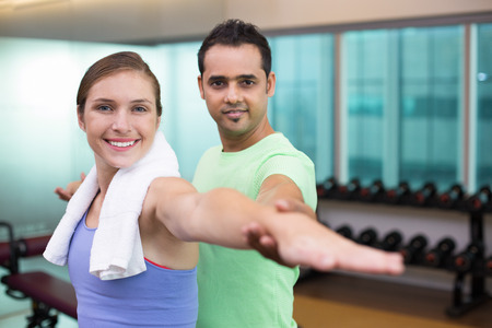 Young male trainer corrects woman hands position in gym with blurry equipment in background. They are smiling to camera. Stock Photo