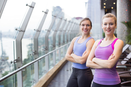 Two smiling young women wearing sportswear, looking at camera and standing with arms crossed on balcony with glass fence and view of city outside