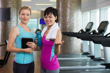 extending: Two smiling at camera young women wearing sportswear and standing in gym with training equipment in background. They are holding tablet and water in bottle. One woman is extending hand to camera.