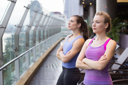 glass fence: Two serious young women wearing sportswear, looking aside and standing with arms crossed on balcony with glass fence and view of city outside