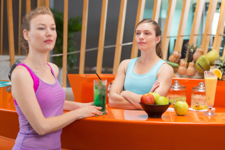 both sides: Serious young woman with arms crossed looking at another slightly blurred woman in foreground looking aside. They are standing at both sides of fitness bar counter with apples and cocktails in gym.