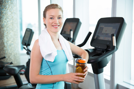 Portrait of young Caucasian woman with towel standing near treadmill, holding water bottle and smiling at camera. Fitness concept