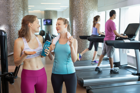 Two happy young Caucasian women talking after training in gym. Man and woman running on treadmills in background