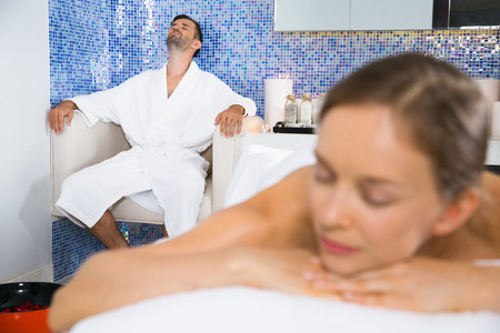 Portrait of young Caucasian man wearing bath robe sitting on arm chair with eyes closed and relaxing after spa treatment. Young woman lying on massage table and waiting for massage Stock Photo