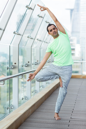 Young Indian man wearing sport clothes and doing yoga exercises on open terrace of modern fitness center. Yoga concept