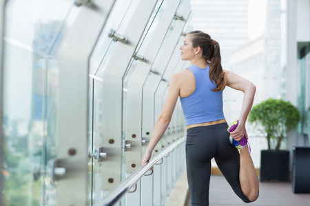 flexing: Portrait of young Caucasian woman doing exercises on open terrace of modern fitness club. Fitness concept Stock Photo