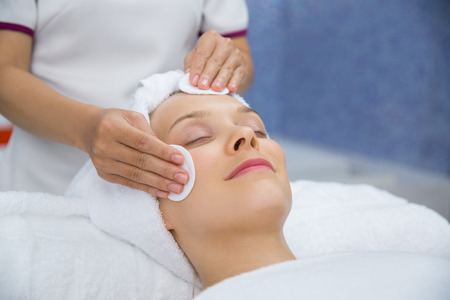 Young Caucasian woman getting facial treatment in spa salon. Beautician cleaning woman face with cotton pads Stock Photo