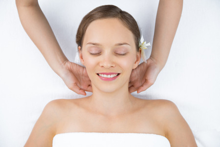 Top view of happy young woman with exotic flower in hair lying on back and keeping her eyes closed while therapist massaging her neck