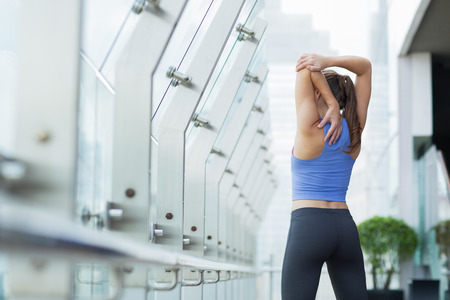 Back view of young Caucasian woman doing exercises on open terrace of modern fitness club, stretching arms. Healthy lifestyle concept