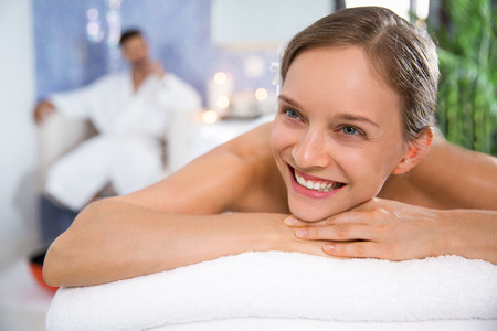 bath robe: Portrait of happy young Caucasian woman lying on massage table in spa salon and relaxing. Man wearing bath robe sitting in background Stock Photo