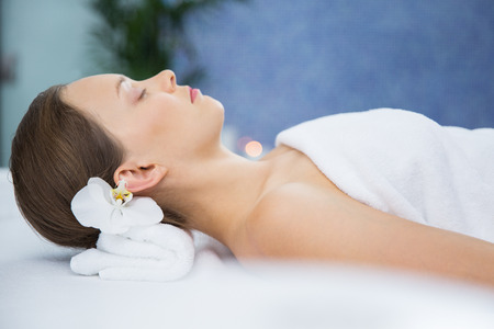 keep an eye on: Portrait of young Caucasian woman with exotic flower in hair lying on massage table, keeping her eyes closed, relaxing after spa treatment in spa salon. Relaxing concept