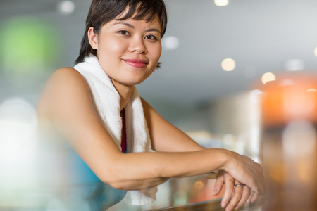 Young Asian woman with towel around her neck standing in hall of modern fitness center and smiling at camera. She relaxing after training