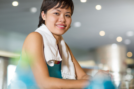 Young Asian woman with towel around her neck standing in hallway of modern fitness center and smiling at camera